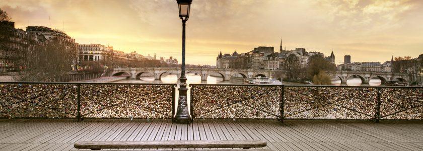 ławka i latarnia na tle mostu nad rzeką